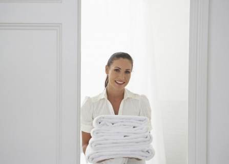 portrait-of-happy-young-woman-carrying-folded-towels-at-home